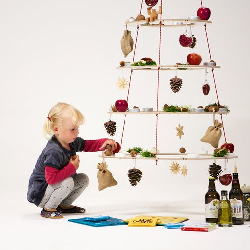 A child decorates the sustainable Christmas tree Josef with nuts, apples and pine cones