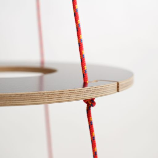 The ecological Christmas tree is made from plywood rings with a black surface and red ropes