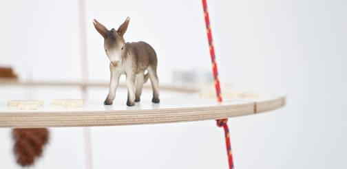 A toy donkey stands as a tree decoration on a white plywood ring.