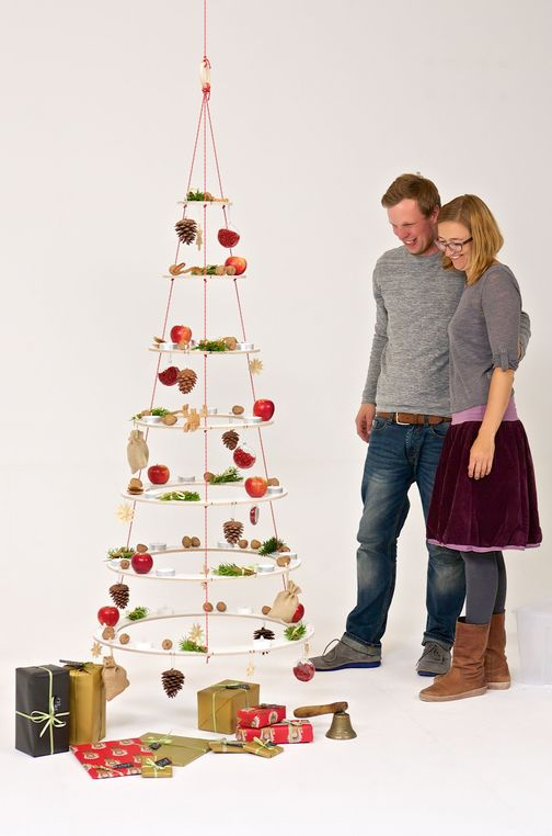 Happy couple looks at his decorated Josef, the Christmas tree made from wood and knotted ropes.