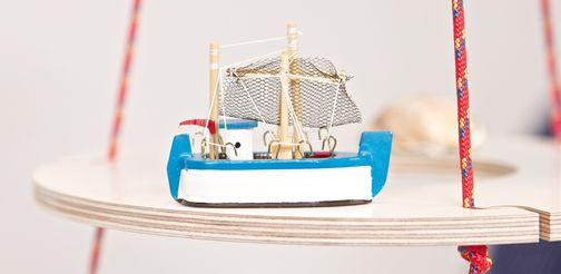 A small fishing boat as a Christmas decoration on a plywood ring.