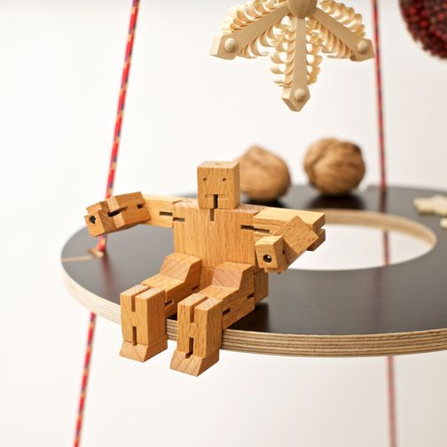 Josef in black with red ropes decorated with nuts, wooden stars and a toy robot made of wood.