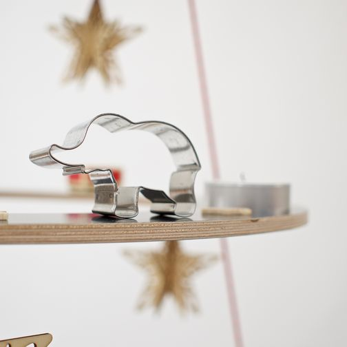 An elephant cookie cutter stands as a Christmas tree decoration on a black plywood rings.